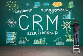 Man drawing on chalk board CRM doodles and written CRM Customer Management